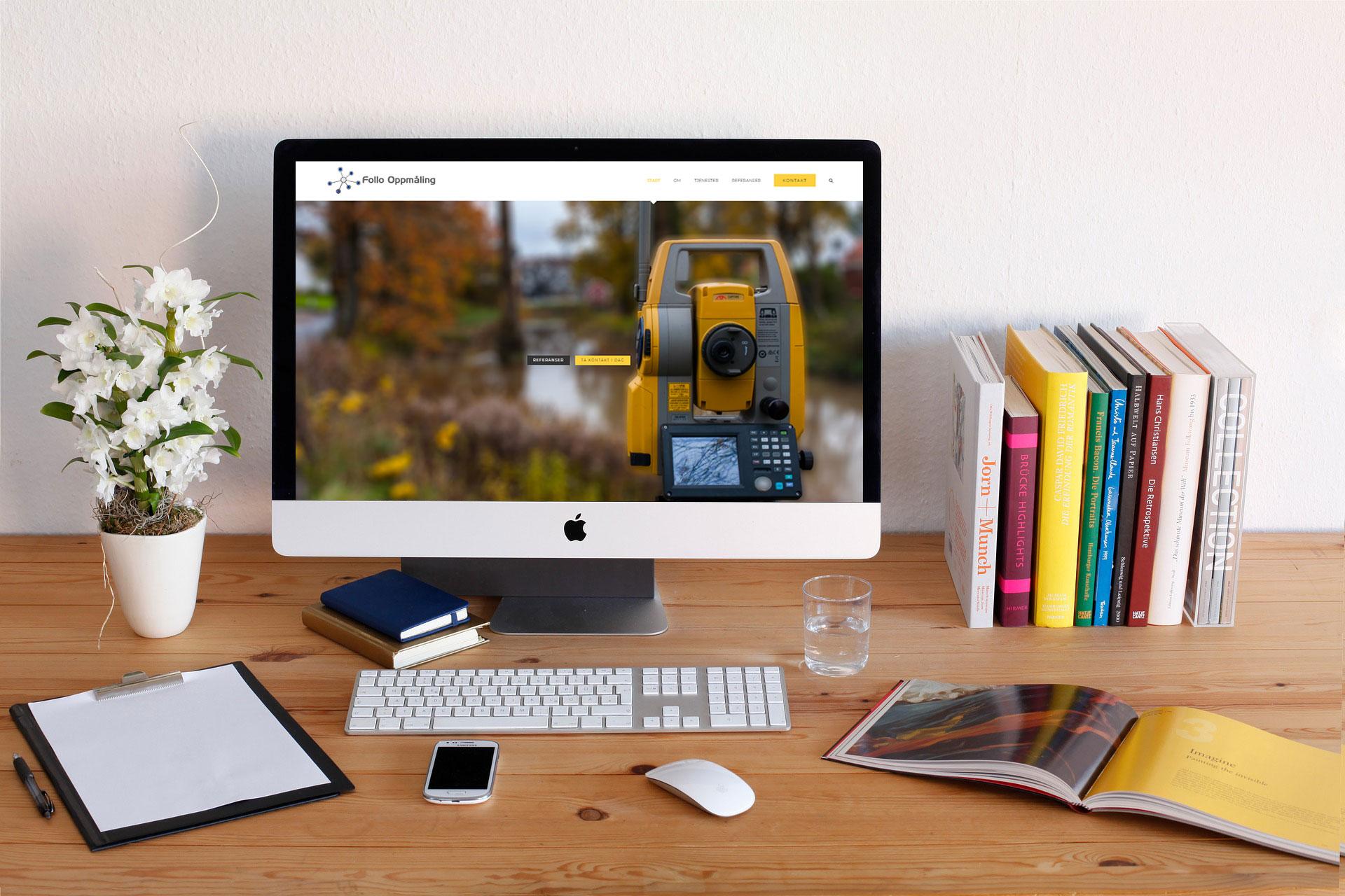 Pult med skrive saker, noen bøker, blomst og skjerm med tilhørende mus og tastatur. På skjermen er Follo oppmåling nye nettside