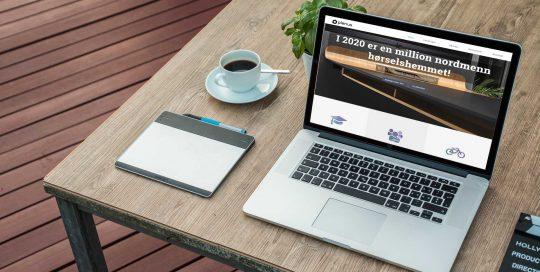 ryddig kaffe bord med laptop som viser Plenus sine nettsider